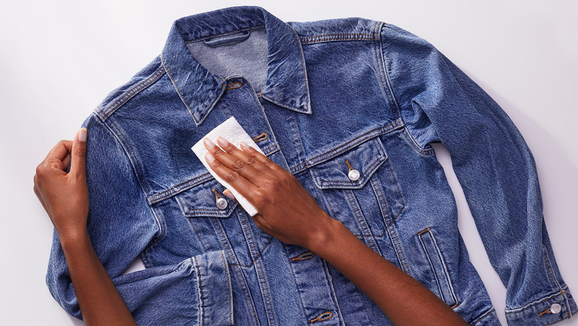 A person removing excess stain from a denim jacket with a paper towel