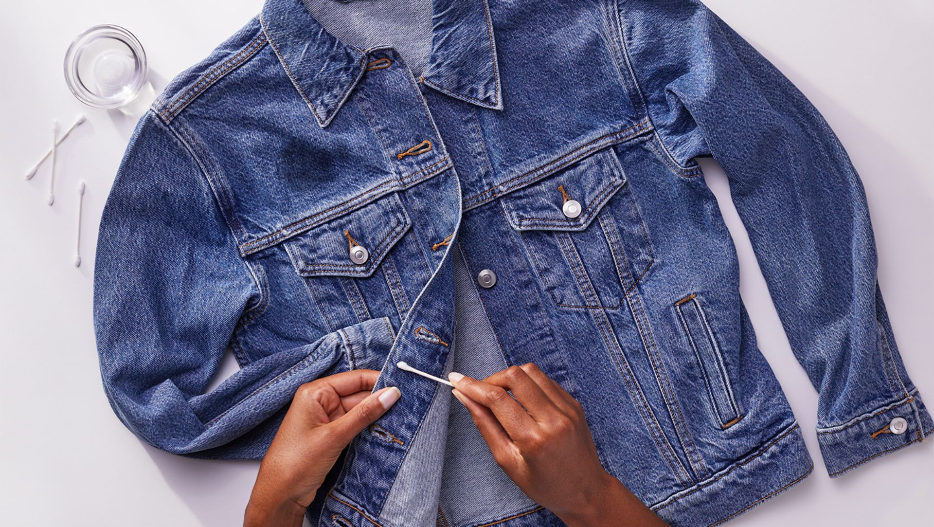 A person removing excess stain from a denim jacket with a cotton swab