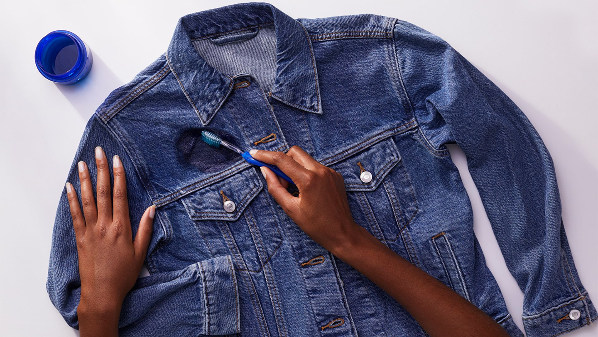 A person pretreating a denim jacket with Tide liquid laundry detergent and a toothbrush
