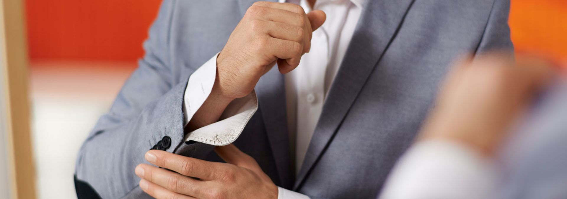 A man in grey suit adjusting his cuff-links