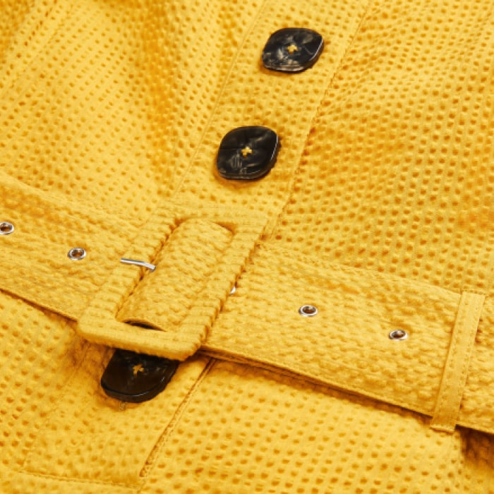 Close up of buttons on a dress and a belt