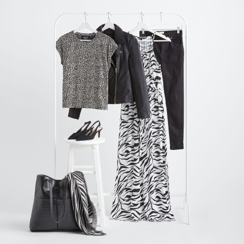 Stitch Fix X County Capsules Cheshire popular women's clothing featuring a zebra print dress, a black leather jacket, black jeans, black heeled shoes, a black leather purse and a zebra print scarf.