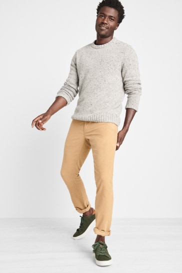 Stitch Fix men's clothes including a grey sweater and tan pants with green sneakers.