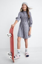 Model wearing Stitch Fix Kids clothes including a grey print dress, grey beanie hat, knit socks and cream sandals.