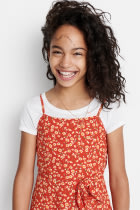 Model wearing Stitch Fix Kids clothes including white tee under a orange floral jumpsuit.