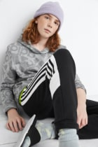Model wearing Stitch Fix Kids clothes including grey hoodie shirt, black joggers, grey socks and beanie, and black sandals.