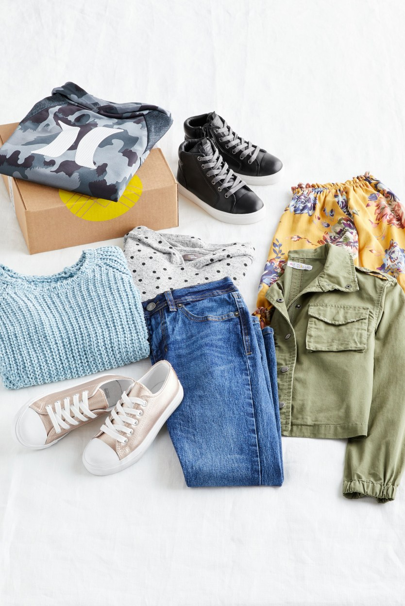Folded Stitch Fix kids casual clothes including shoes, a sweater, a jacket and medium wash jeans.