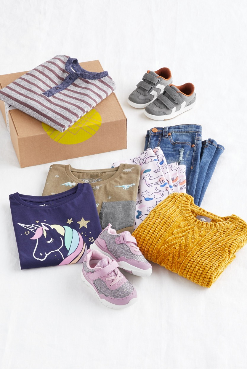 Folded Stitch Fix kids casual clothes including gold sweater, blue jeans, unicorn tee shirt, pink leggings and shoes.