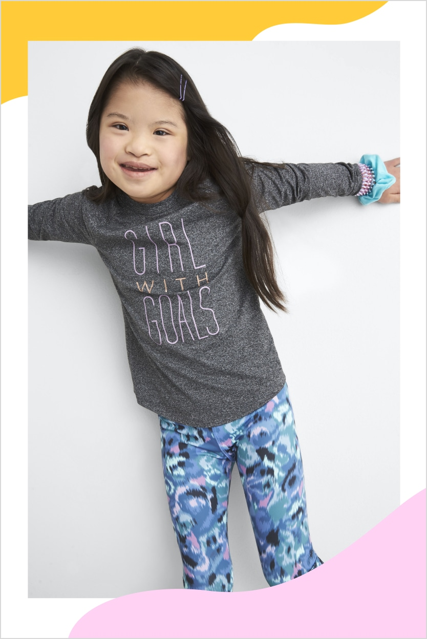 Model wearing Stitch Fix kids clothes including pink and blue bottoms and grey and pink long sleeve graphic tee.