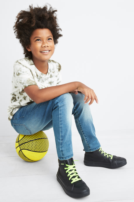 Model wearing Stitch Fix Kids clothes including white printed tee, light wash jeans and black sneakers.