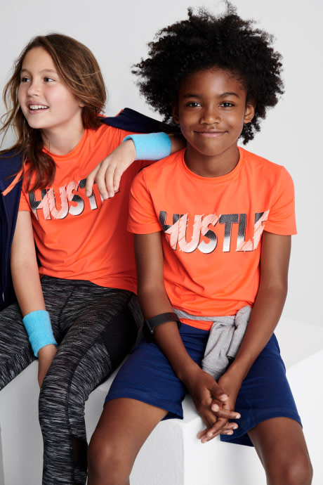 Two models wearing Stitch Fix Kids clothes including orange tees, outerwear, accessories, blue shorts and camo print leggings.