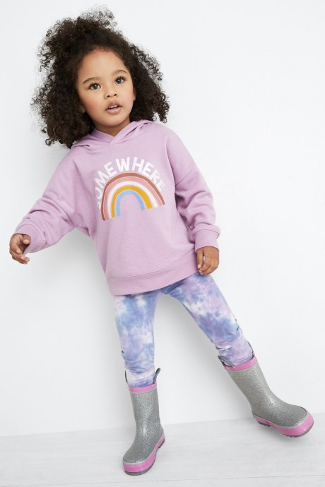 Model wearing Stitch Fix Kids clothes including pink rainbow hoodie sweatshirt, blue and white leggings and grey galoshes.