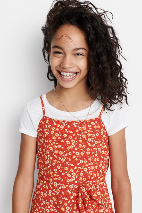 Model wearing Stitch Fix Kids clothes including white tee under an orange floral jumpsuit.