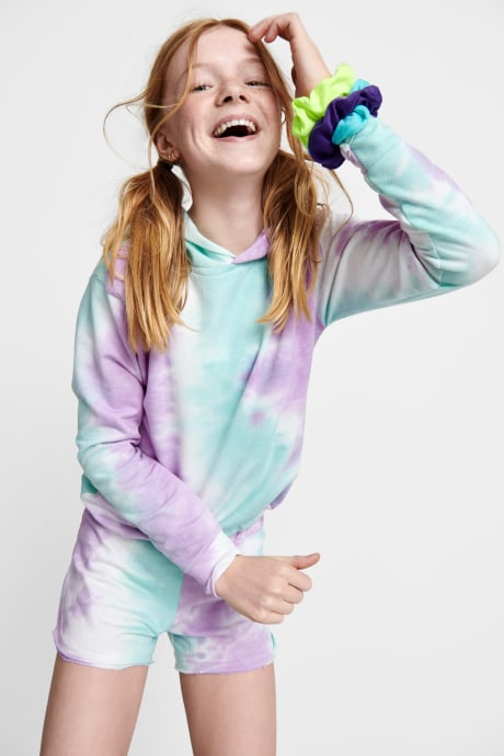 Model wearing Stitch Fix Kids clothes including blue and purple tie-dye hoodie shirt and shorts with hair ties.