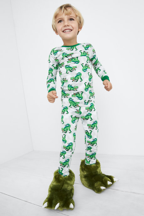 Model wearing Stitch Fix Kids clothes including dinosaur print pajamas with green monster slippers.