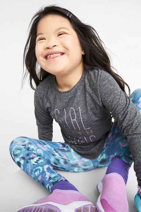 Model wearing Stitch Fix Kids clothes including grey long sleeve shirt, blue patterned leggings and purple sneakers.