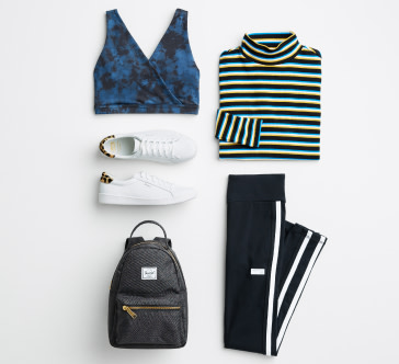 Activewear clothing including a blue and black bra top, black and white striped mock neck shirt, white sneakers, grey backpack and black pants.