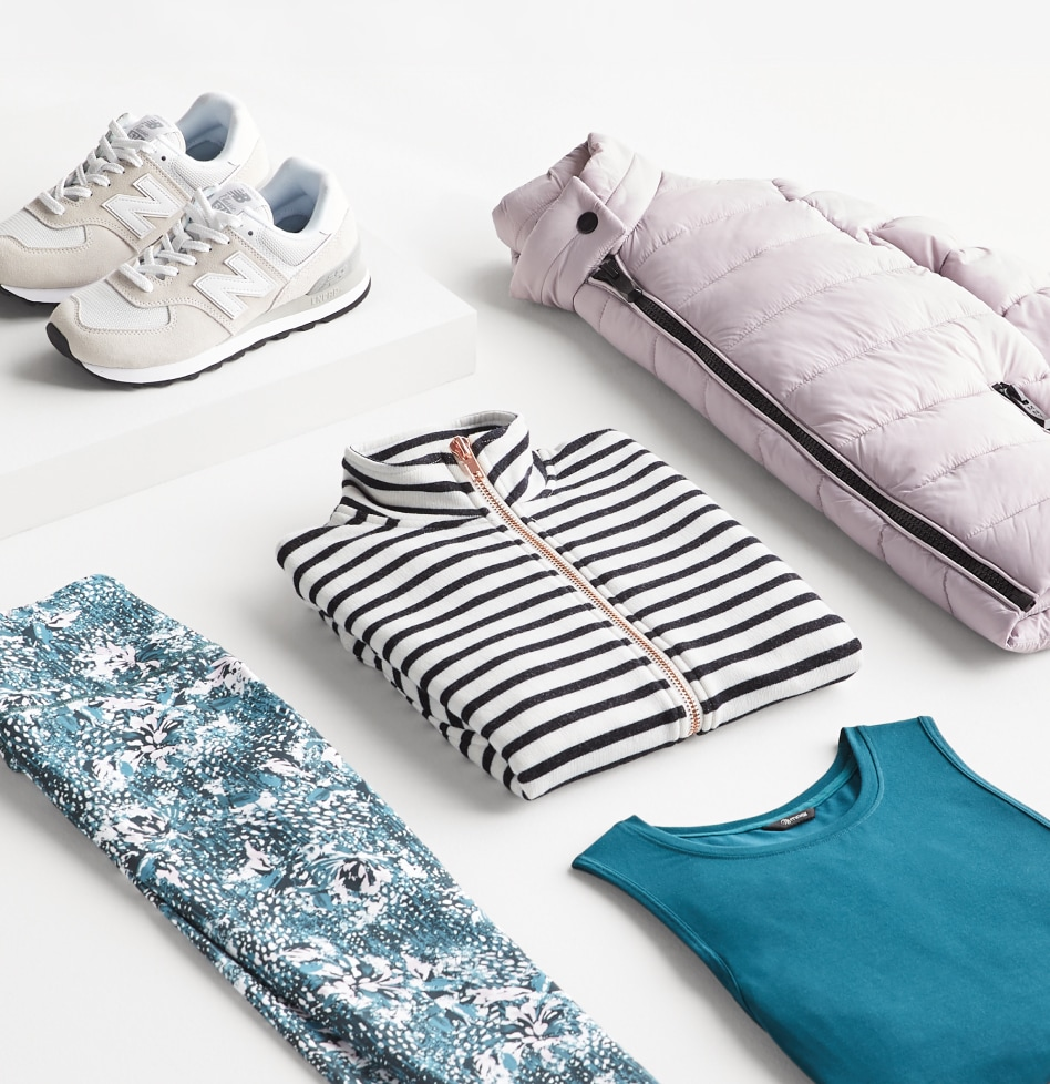 Activewear outfit including white sneakers and puffer jacket, black and white zip up, blue floral pants and a teal tank.