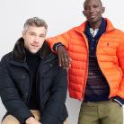 Black and orange men's athleisure puffer jackets over dark tops.