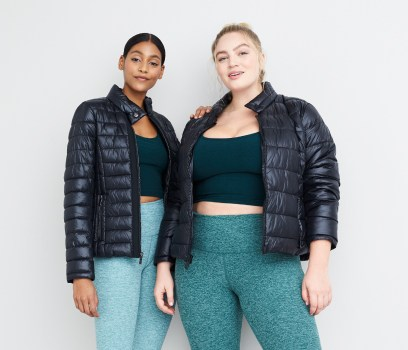 Plus size athleisure clothing including navy puffer jackets, teal workout tops and leggings.