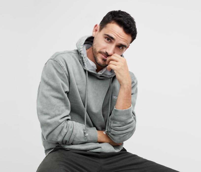 Men's activewear clothing including a grey men's hoodie sweatshirt and dark pants.