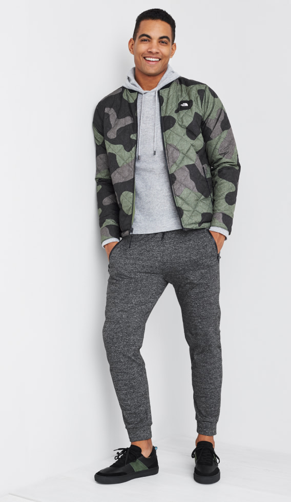 Men's athleisure clothing including a grey mens hoodie, camo jacket, grey joggers and black sneakers.