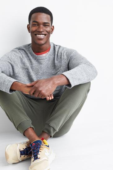 男人穿着灰色运动上衣,深色土色运动裤和鞋子。