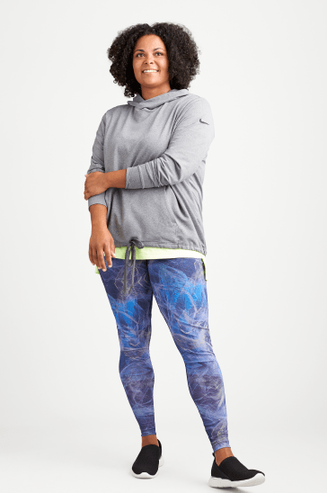 Plus size athleisure clothing including a grey hoodie sweatshirt, blue plus size leggings and sneakers.