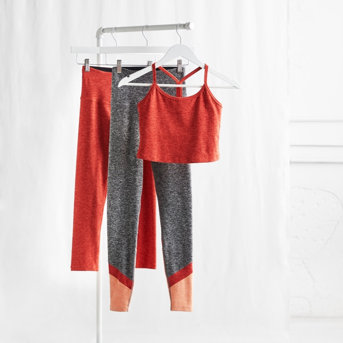 Plus size activewear clothing including orange and grey leggings and orange crop top.