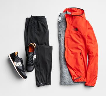Men's jogger pants in black, black athletic shoes, grey shirt and orange jacket.