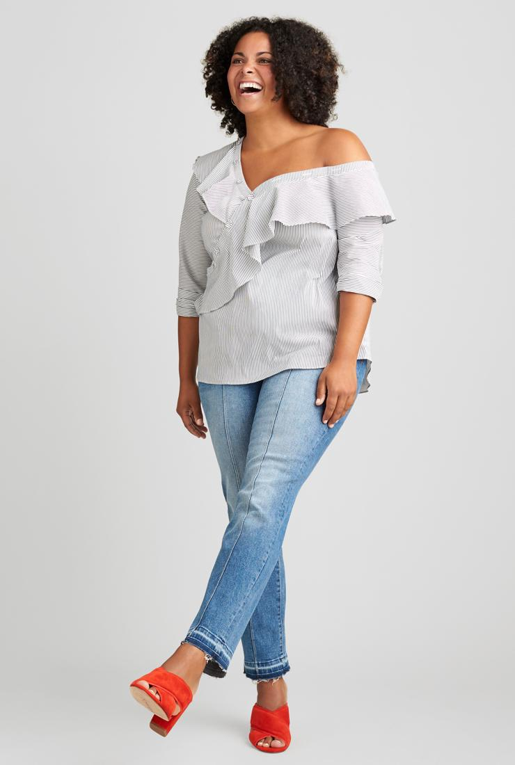 Pale off-the-shoulder top with ruffle detail, jeans and red shoes.
