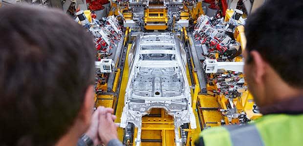 Orange robots spot welding a Jaguar XJ on the Jaguar Experience Manufacturing Tour at Castle Bromwich