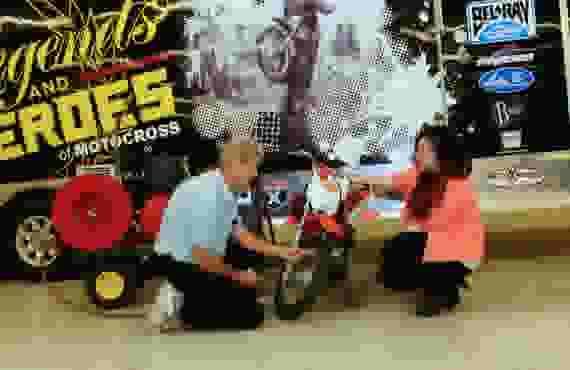 Man helping woman fill dirt bike tire