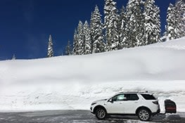 Stowaway cargo carrier on a white SUV on snow mountain
