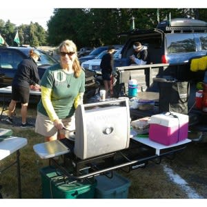 Stowaway hitch grill station - Ducks fan woman cooking at grill
