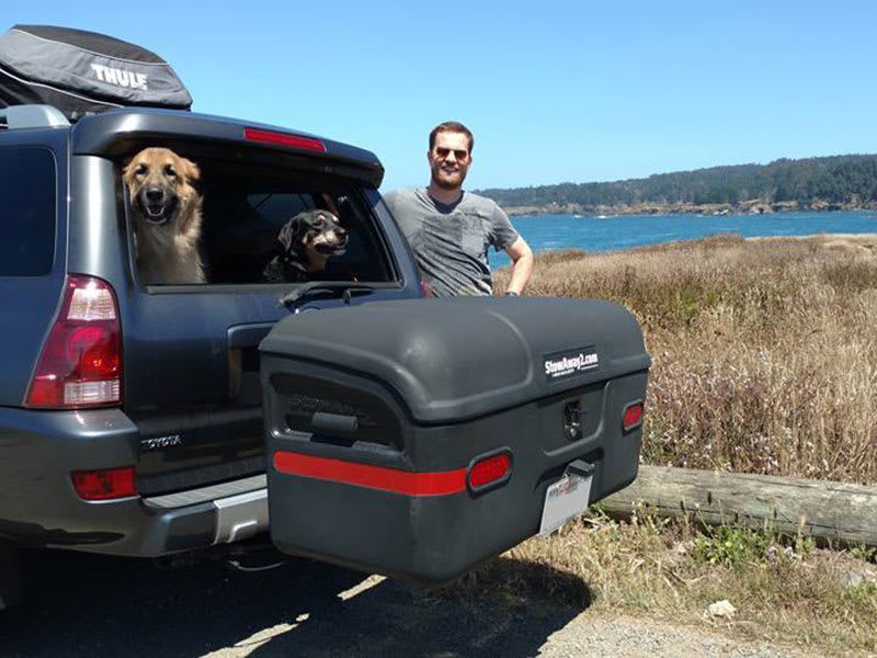 Man with two dogs and a Stowaway Cargo Carrier during Thanksgiving Holiday Travel
