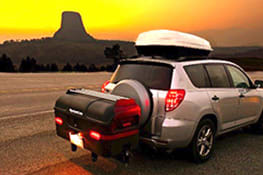 Stowaway cargo carrier on gray SUV driving through the canyon in sunset