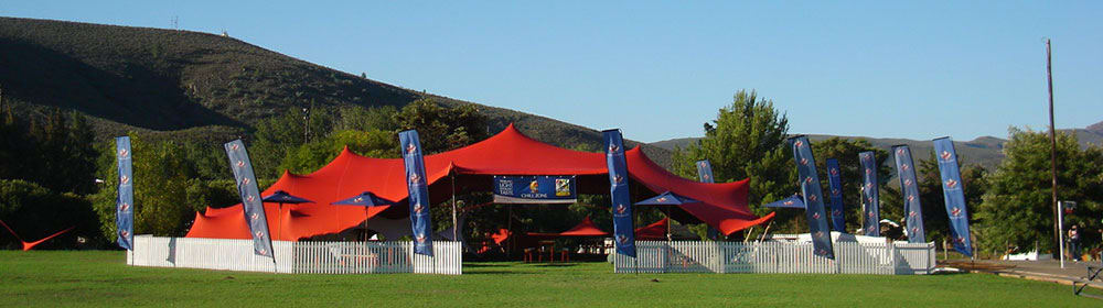 blue sky and green grass over a stretch tent