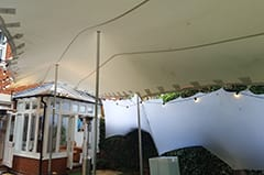 white stretch tent birthday garden party attahced to building