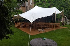 white stretch tent garden party attached to house tables and chairs