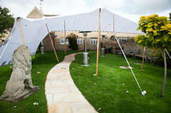 A shot of a stretch tent post reception: rigged directly to the house, with a garden wall inside the tent. Sides both down and up!