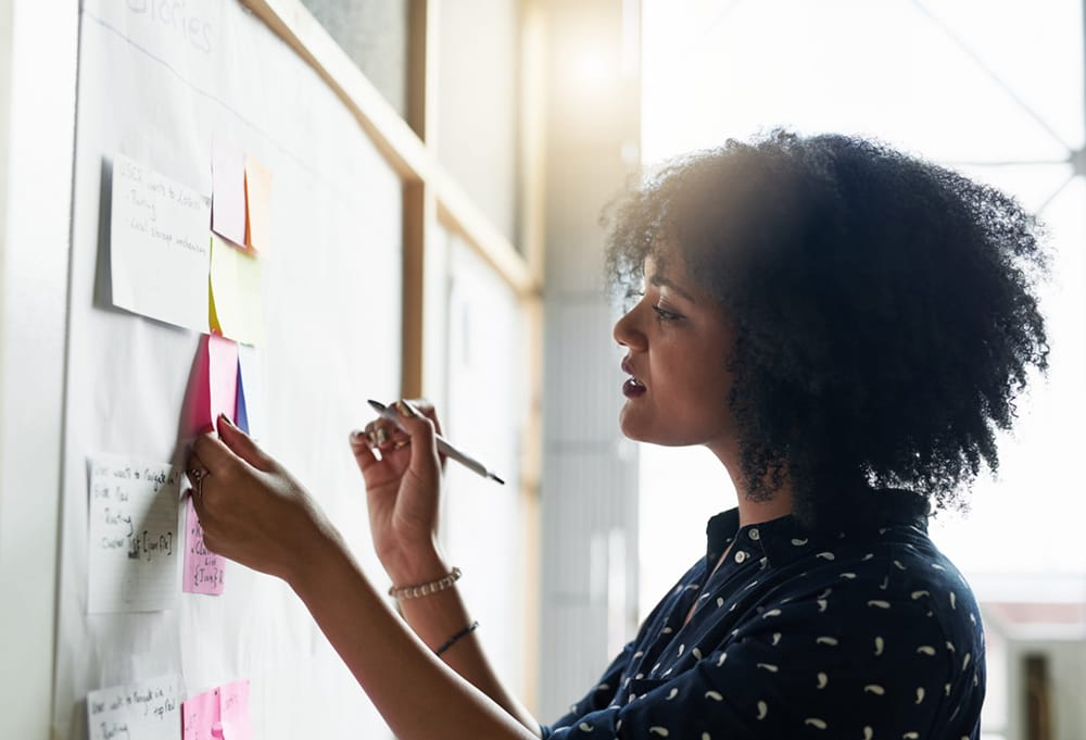 Woman writing on post-it notes and adding to a whiteboard.