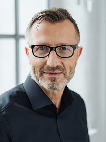 Mann mit Brille lächelt in Kamera