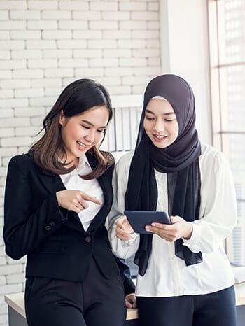 Junge Mitarbeitende schauen auf Tablet