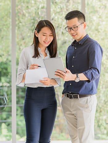 Mitarbeitende tauschen sich aus mit Tablet in der Hand