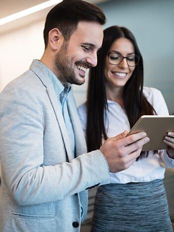 Mitarbeitende blicken auf Tablet