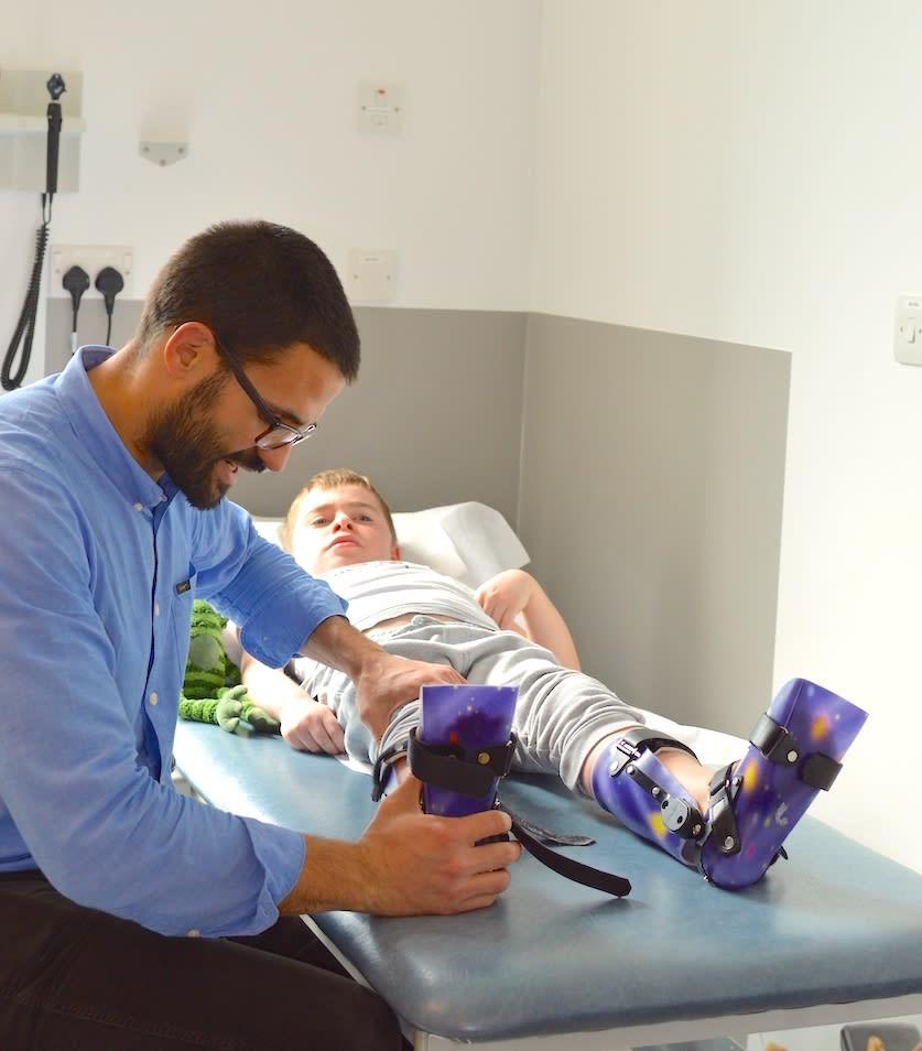 A doctor treating a boy with leg splints