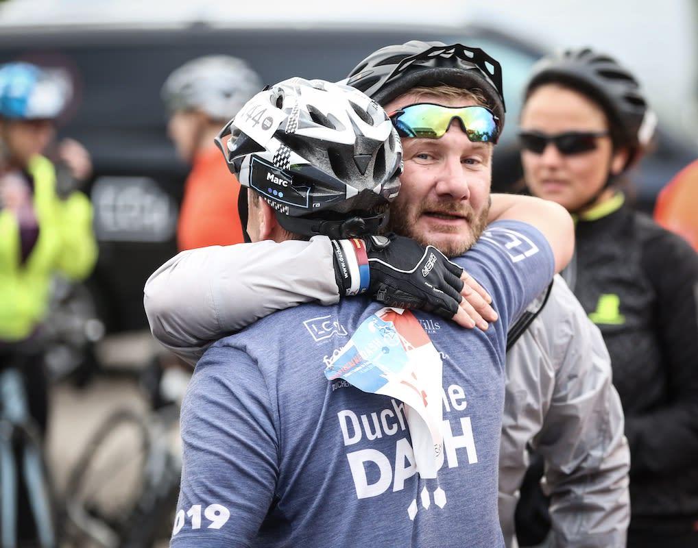 Two Duchenne Dash cyclists hugging