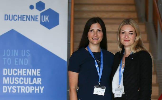 Alex Johnson and Emily Crossley standing next to Duchenne UK banner