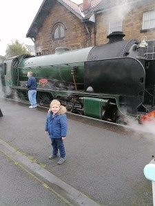 Edward, who has DMD, standing in front of a steam train